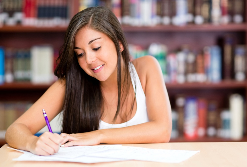 Beautiful young woman studying at the library