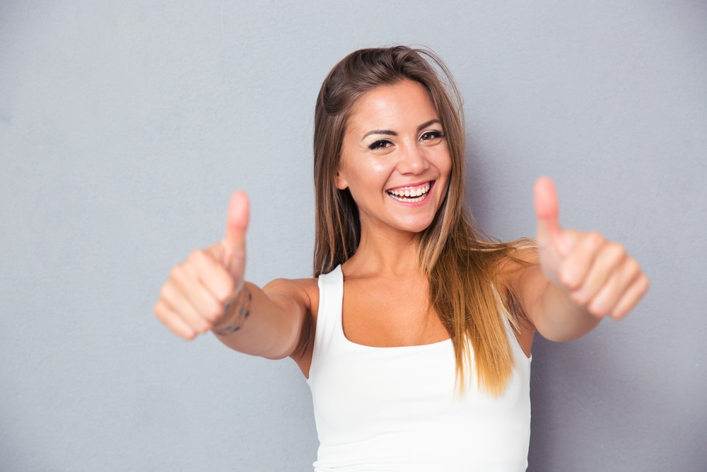 Cheerful lovely girl showing thumbs up over gray background. Looking at camera