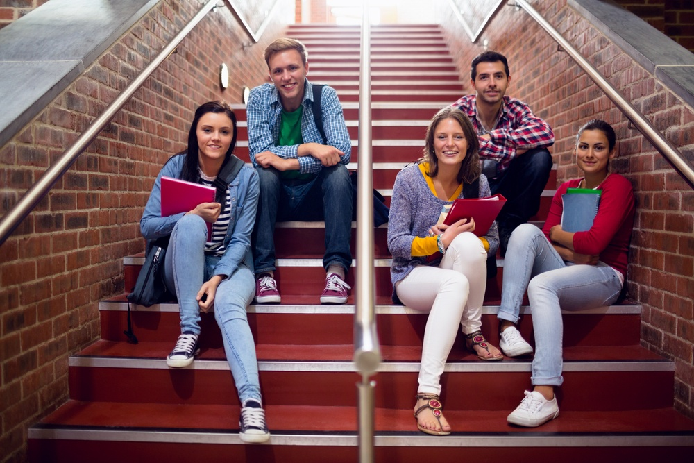 Group portrait of young college students sitting on stairs in the college