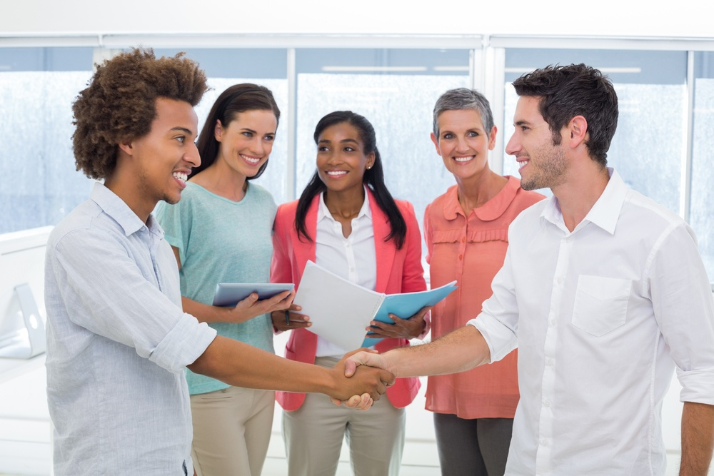 Attractive businessmen shaking hands at work in front of coworkers